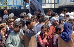 Afegãos fazem fila para sacar dinheiro em agência bancária em Cabul