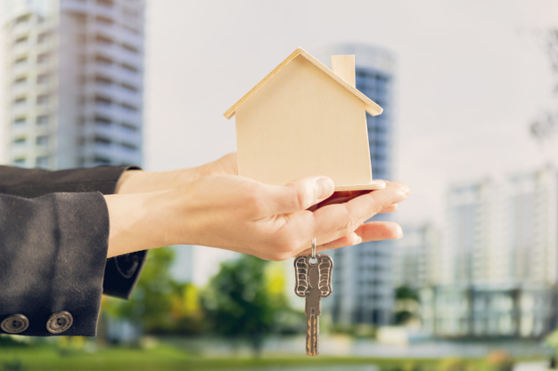 close up female s hand holding wooden house model keys against blurred building backdrop_23 2148038696