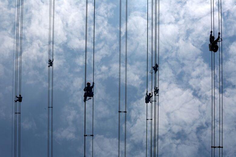 Trabalhadores atuam em cabos de linha de transmissão de energia em Dongguan, na China