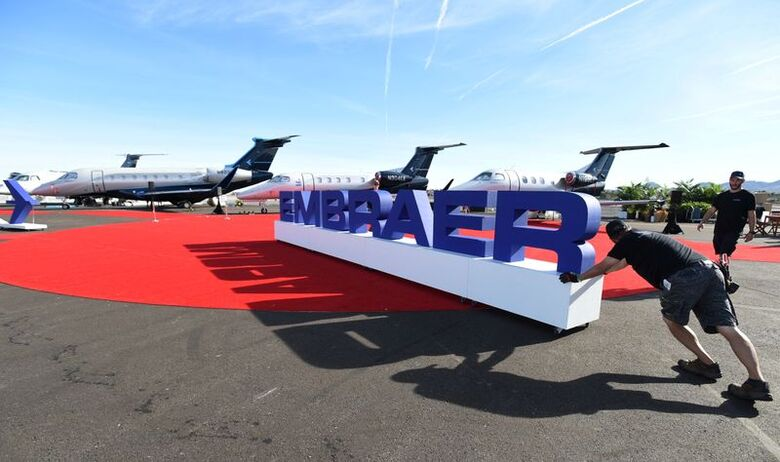 Funcionários ajeitam letreiro da Embraer durante exposição em Las Vegas