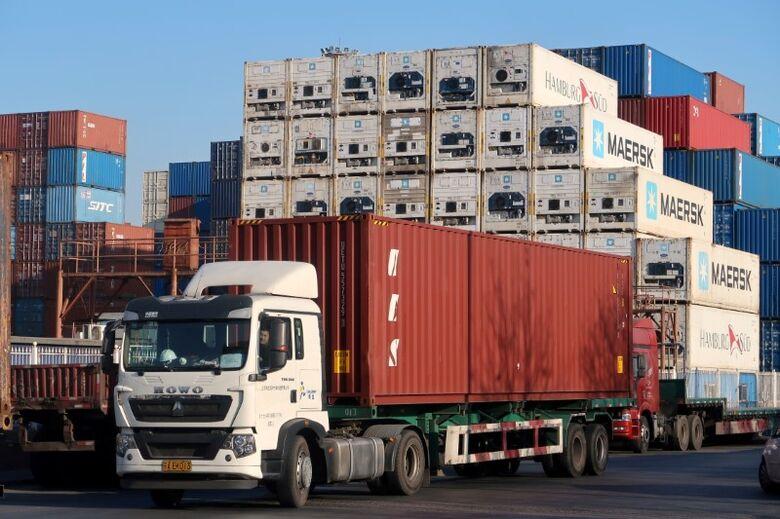 Caminhão carregando contêiner em centro de logística perto do porto de Tianjin, China
