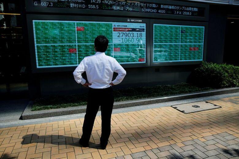 Painel eletrônico mostrando o índice Nikkei em corretora de Tóquio