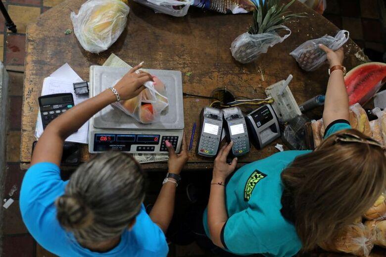 Funcionários pesam frutas em mercado de Caracas